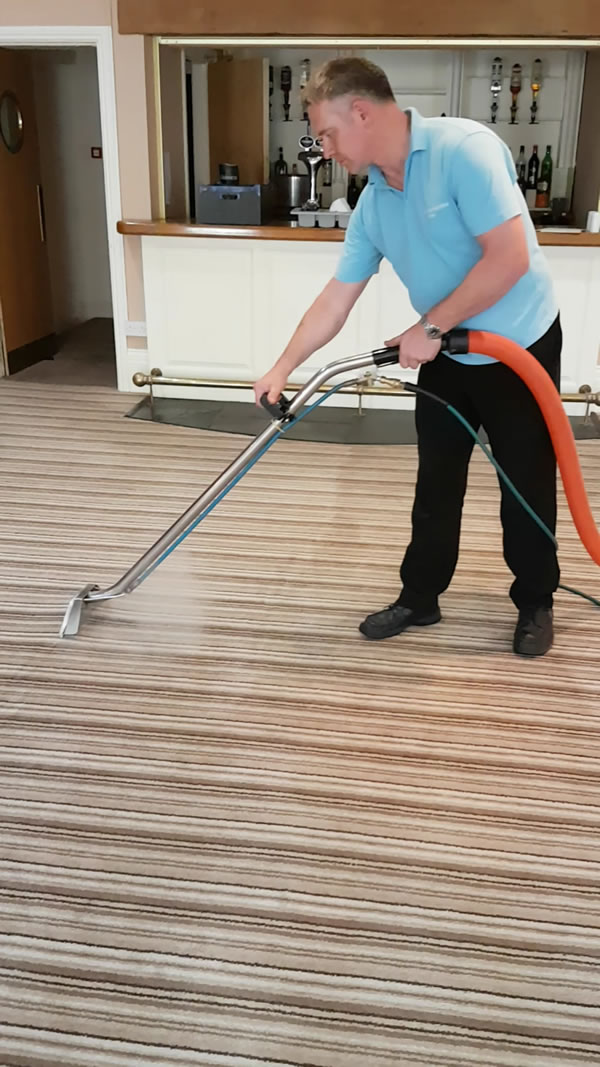 James, the owner of Carmarthenshire Carpet Care steam cleaning a carpet in a bar area.