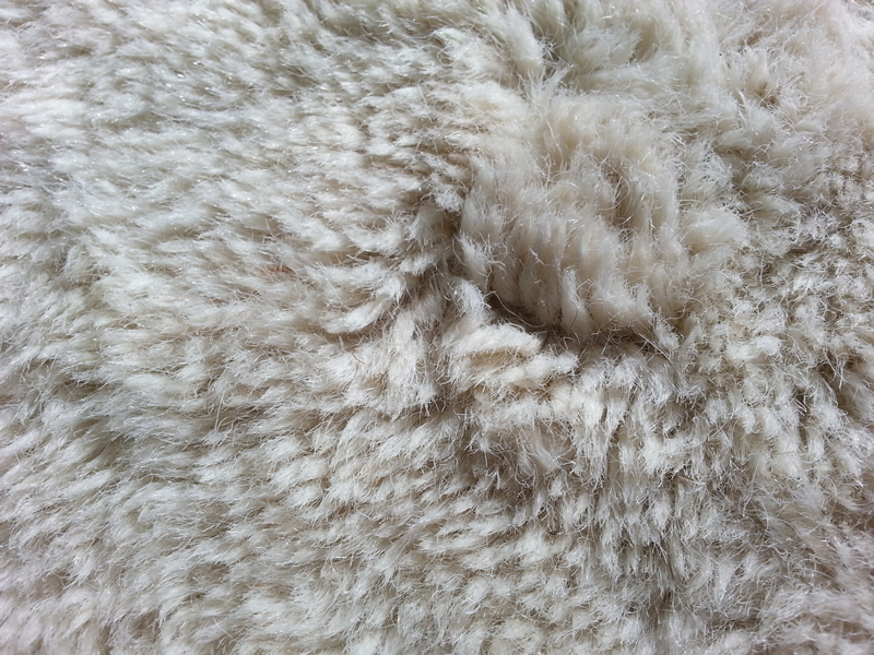Image shows close-up of a white heavy shag rug.