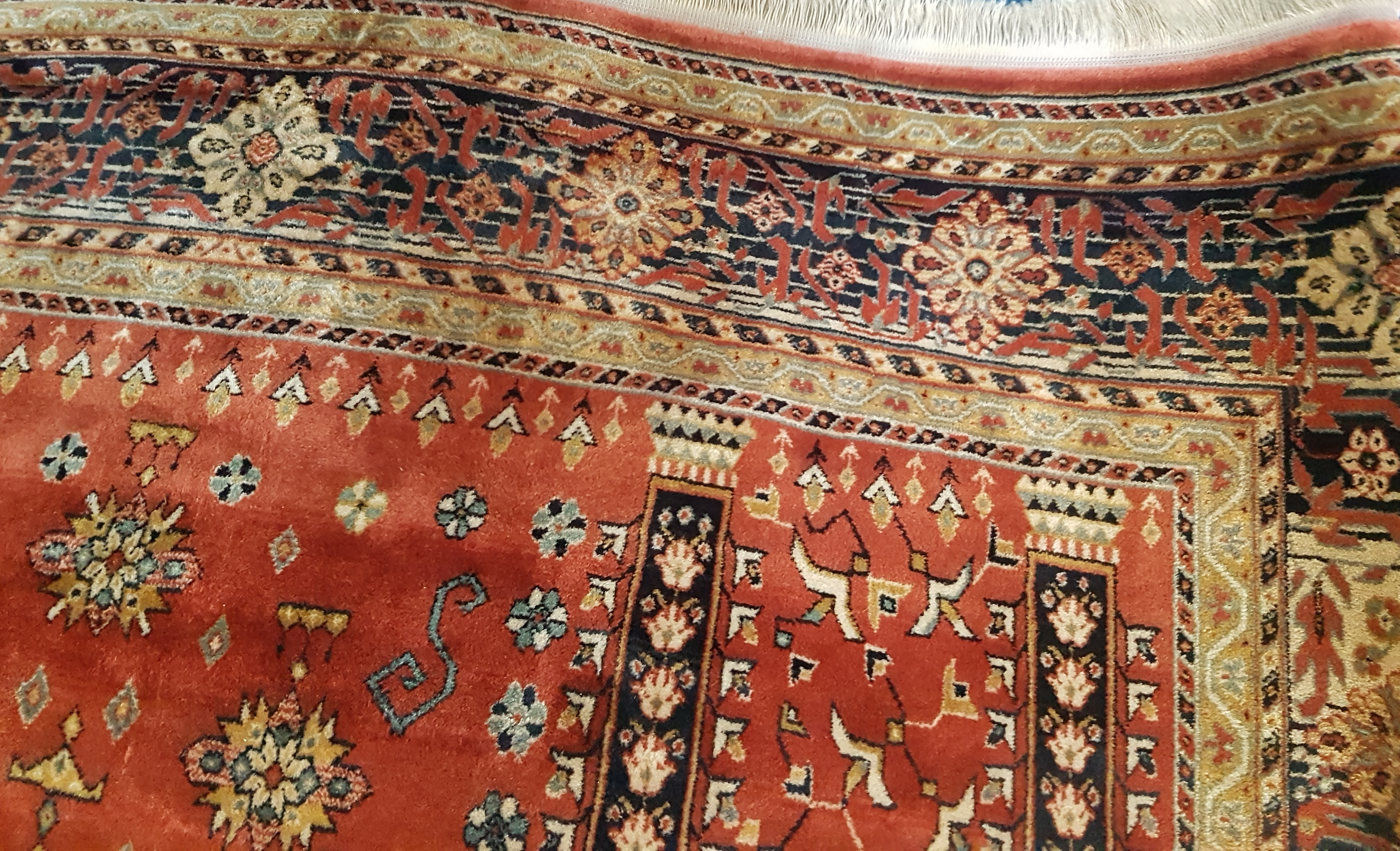 Close-up of an ochre coloured patterned rug.