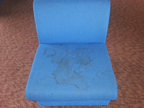 Image shows a badly stained upholstered chair before cleaning.