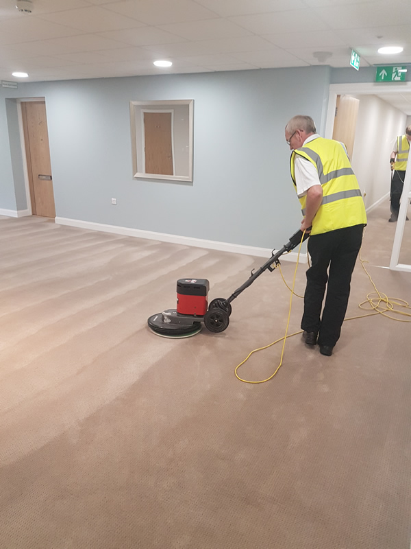 Cleaning a carpet in a commercial space.